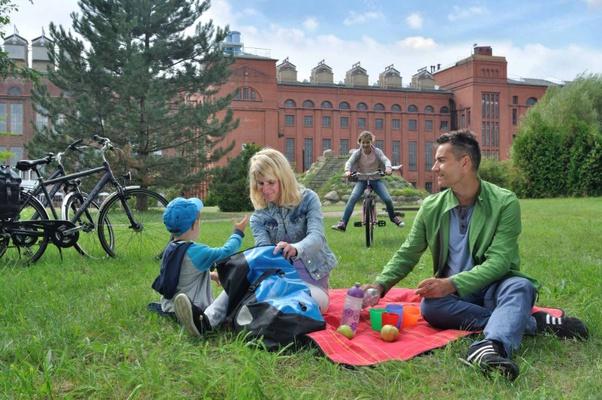 Familie beim Picknick vor dem Backsteinbau der Energiefabrik Knappenrode / Foto: Tourismusverband Lausitzer Seenland, Nada Quenzel
