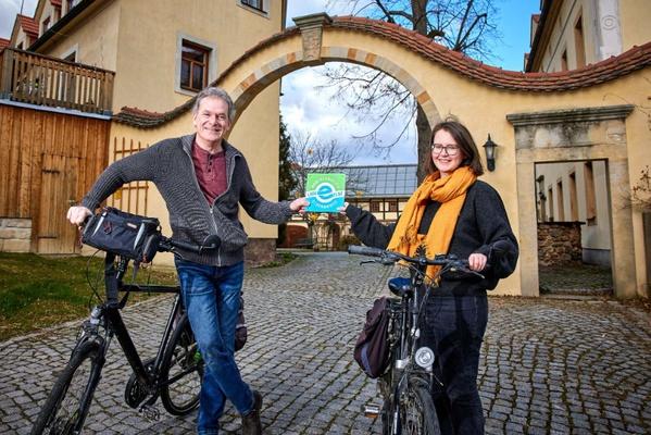 Elberadweg-Koordinatorin Heike Grunow übergibt Hotelinhaber Roland Taubinger vom Landhotel Gut Wildberg die neue Plakette. Foto: Marko Förster