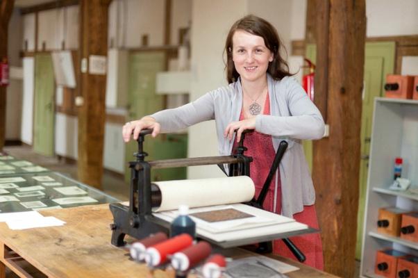 Maria Pretzschner, Museumspädagogin der Festung Königstein gGmbH, leitet Kreative an der historischen Druckerpresse an, Foto Sebastian Thiel